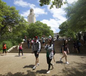 Students walking along the steps in front of the Tower on a sunny day.