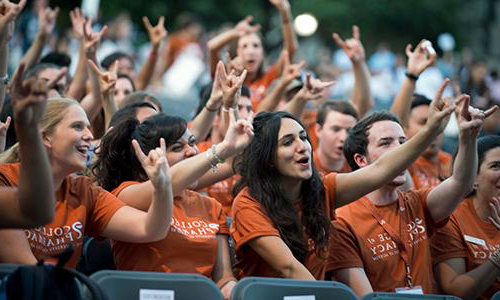 Students at Gone to Texas wear orange shirts while giving the hook 'em sign.